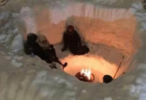 Winter campers gathered around fire it in snow