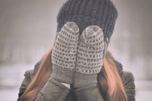 Woman wearing mittens in the cold to stay warm