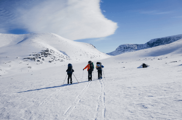 Three men backcountry skiing with climbing skins in the mountains