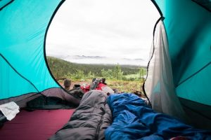 camping with sleeping bag in tent