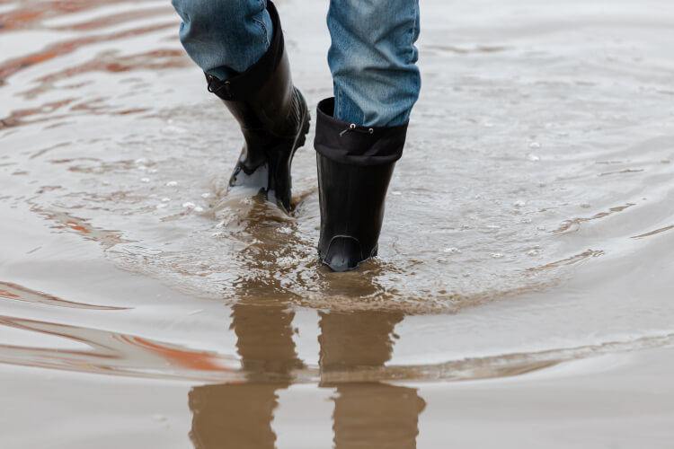 Walking in water in waterproof rubber boots