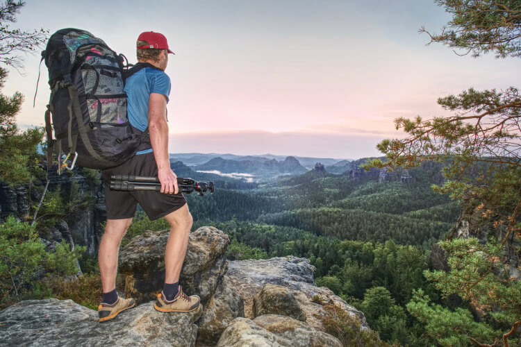 Hiker carrying traveler tripod