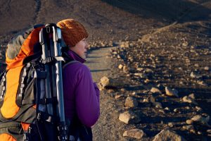 Hiking with tripod attached to backpack