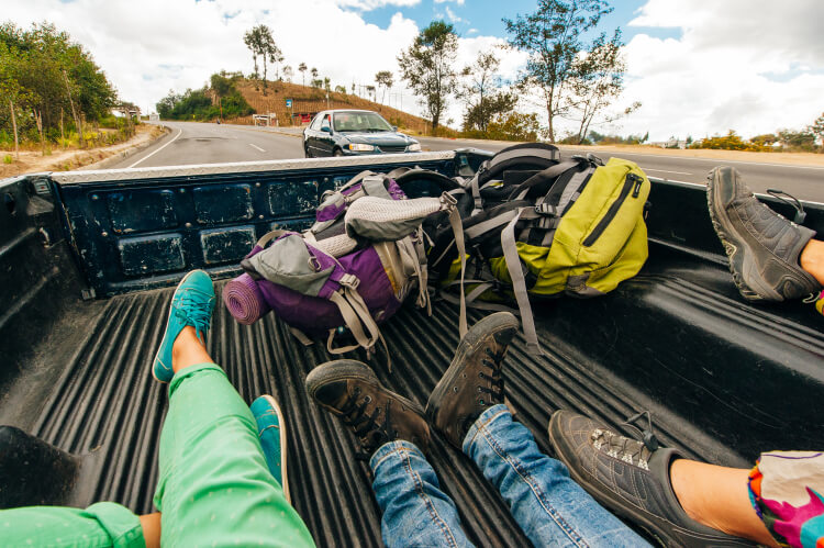 Hikers hitchhiking in back of pickup truck