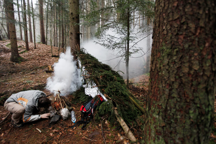 Man lighting fire next to survival shelter