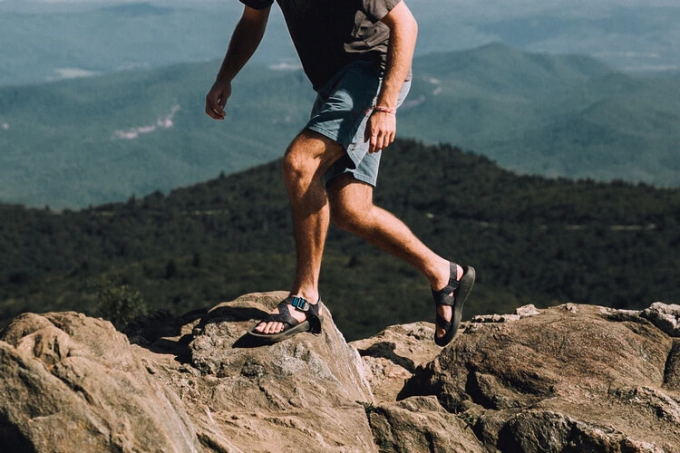 Man wearing Chacos hiking on rocks